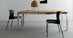 Extendable tables inhardwood with lamp on it and black chairs around