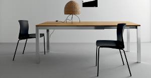 Tavoli estendibili in legno con strana lampada marrone sopra, e due sedie nere intorno