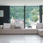 Divano biba salotti colore beige con penisola componibile, su sfondo finestre e boschi